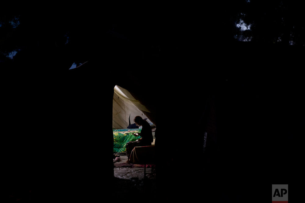 In this Monday, Sept. 12, 2016 photo, a Syrian woman uses her mobile phone inside a tent at the Ritsona camp for refugees and other migrants north of Athens. Residents have access to free wifi services, and keep up to date on developments in their homelands. (AP Photo/Petros Giannakouris)