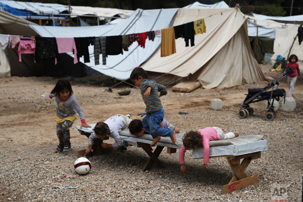 In this Monday, Sept. 19, 2016 photo, Syrian refugee children play on a trestle bed, as a line of washing hangs from tents behind them, at the Ritsona camp for refugees and other migrants north of Athens. (AP Photo/Petros Giannakouris)