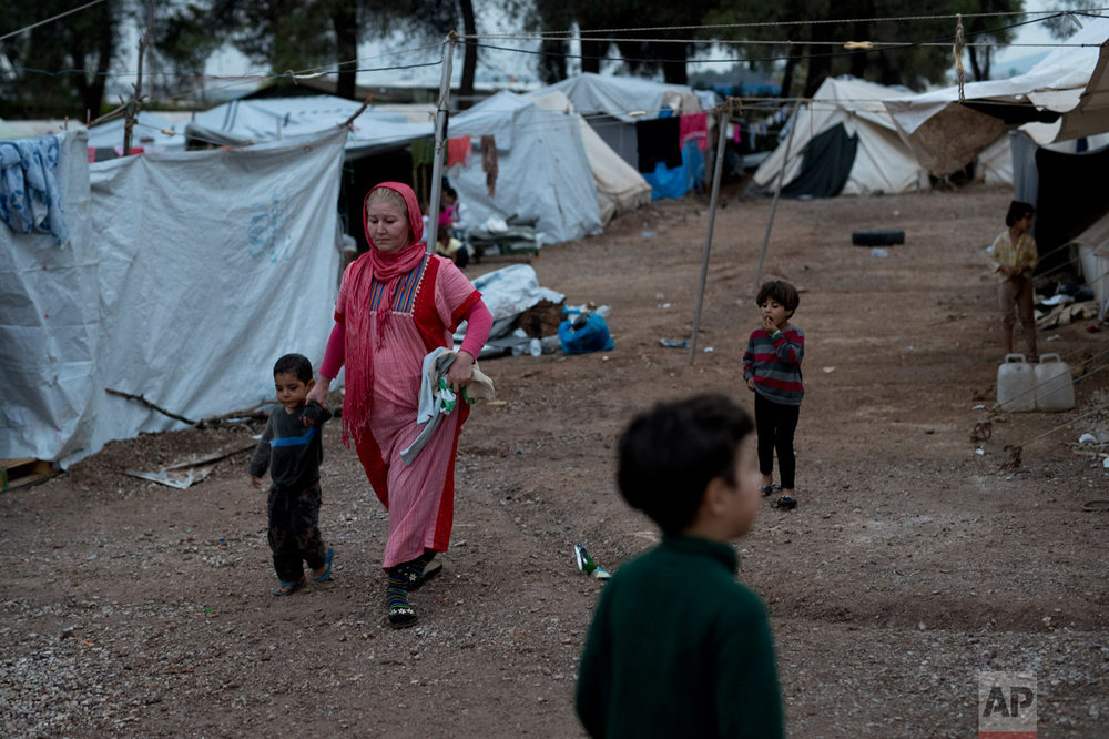 In this Thursday, Sept. 22, 2016 photo, Syrian refugees walk among tents at the Ritsona camp for refugees and other migrants north of Athens. (AP Photo/Petros Giannakouris)