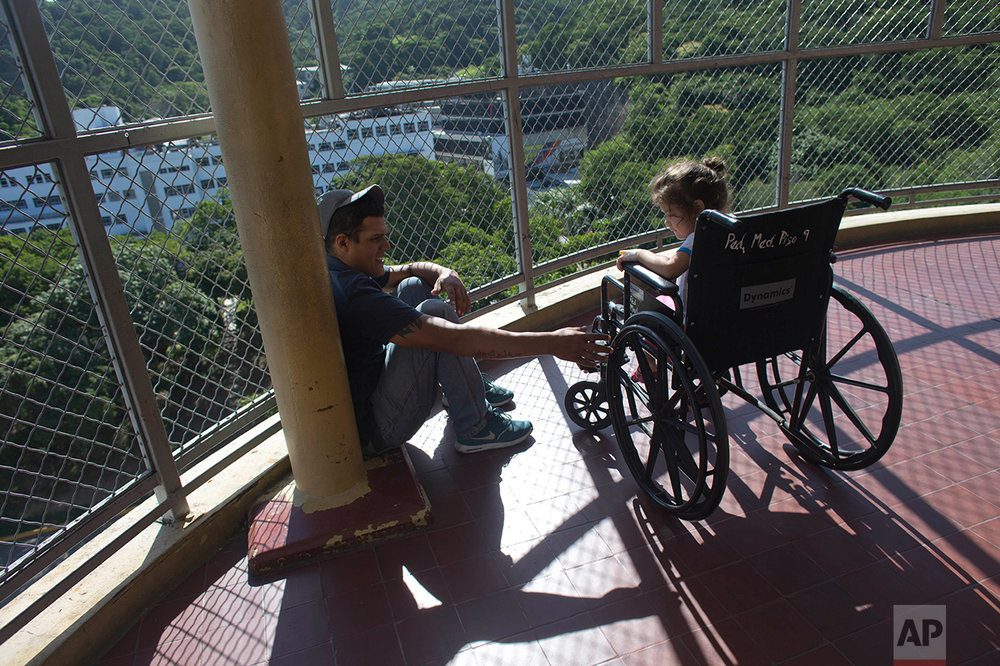In this Aug. 17, 2016 photo, Maykol Pacheco sits with his 3-year-old daughter Ashley, who is recovering from a staph infection, on a balcony at University Hospital in Caracas, Venezuela. Out of options, Pacheco brought his daughter to University Hospital, once one of the best hospitals in South America but lately better known for gang shootings in the operating rooms and stickups in the stairways. (AP Photo/Ariana Cubillos)