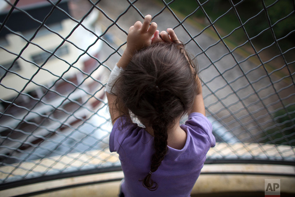 In this Aug. 23, 2016 photo, 3-year-old Ashley Pacheco hooks her fingers around the links of a fence as she gazes out from a hospital balcony, at University Hospital, in Caracas, Venezuela. This is the only place Ashley is able to breathe in fresh air. A scraped knee in mid-July led to a staph infection. There were not enough antibiotics to treat the infection, and so Ashley was kept in the public hospital for two months. (AP Photo/Ariana Cubillos)