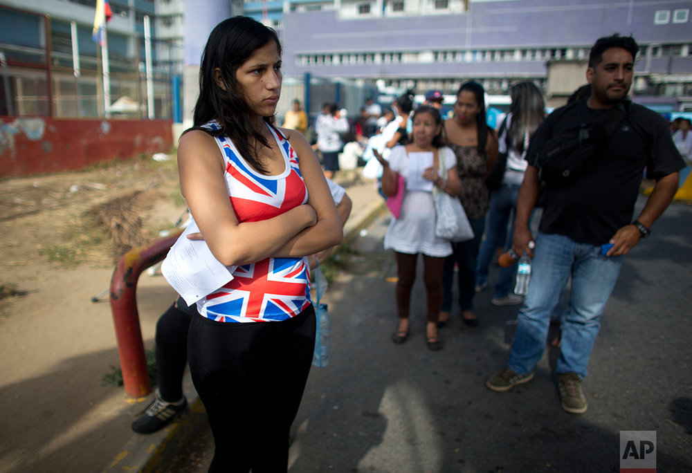 In this Aug. 25, 2016 photo, Oriana Pacheco stands in line to get an appointment for an ultrasound test for her daughter at one of the few public hospitals with a functioning machine, in Caracas, Venezuela. Doctors would not discharge her 3-year-old daughter until she had the test. When Oriana reached the front of the line, the clerk told her the first slot was in November, two months away. (AP Photo/Ariana Cubillos)