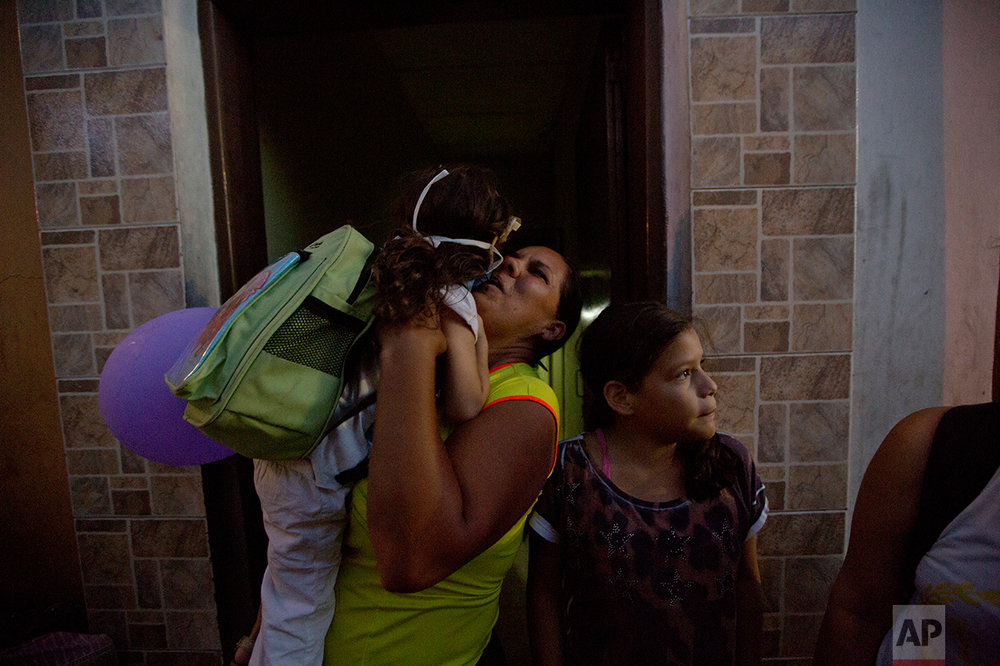 In this Sept. 19, 2016 photo, Ashley Pacheco is welcomed homed after a two-month stay at University Hospital in Caracas, Venezuela. If life in Venezuela has become dangerous for the healthy, it is now deadly for those who fall ill. The government has refused to let in humanitarian aid. So donations of medical supplies sit waiting in warehouses and shipping containers in countries including the U.S., Spain and Panama. (AP Photo/Fernando Llano)