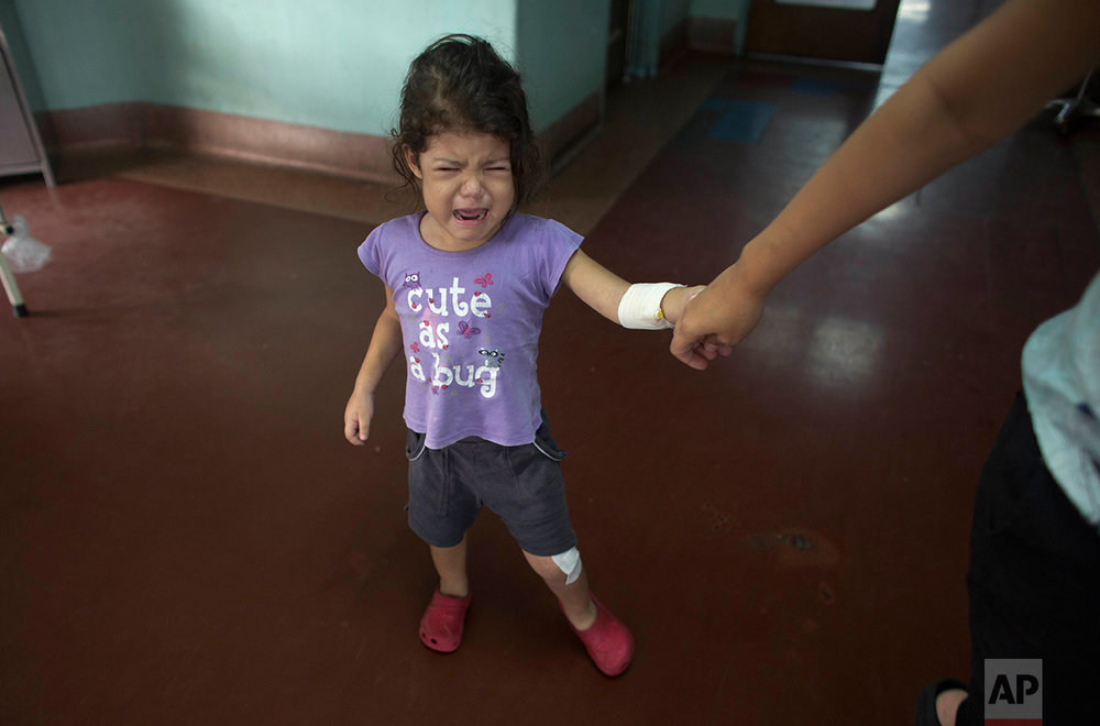 In this Aug. 23, 2016 photo, 3-year-old Ashley Pacheco cries from the pain walking causes in her left leg, as she holds on to her mother's hand, at University Hospital in Caracas, Venezuela. Ashley's parents had been determined to shield her from the chaos engulfing their country. As the public school system collapsed , they sent her to a private Catholic preschool. As food grew harder to find, they made sure she had protein at every meal. When water began coming out of the taps with a foul smell, they boiled it before her daily bath. But their real troubles began when Ashley's scraped knee led to a staph infection. (AP Photo/Ariana Cubillos)