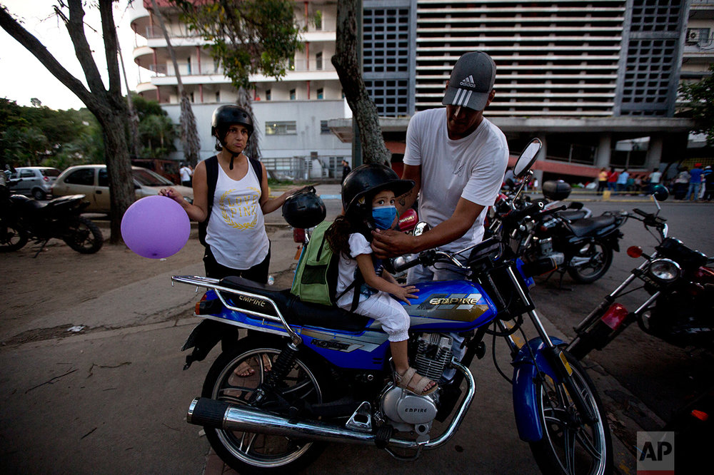 In this Sept. 19, 2016 photo, Maykol Pacheco, places a helmet on his daughter Ashley as they prepare to ride away from the University Hospital in Caracas, Venezuela. Two weeks after 3-year-old Ashley scraped her knee, she was screaming in a hospital, fighting for her life as her family scoured Caracas for scarce antibiotics. Venezuela is running short on 85 percent of basic medicines. As the health care system collapses, the tiniest slips, like a little girl's tumble while chasing her brother, are turning into life-or-death crises. (AP Photo/Fernando Llano)