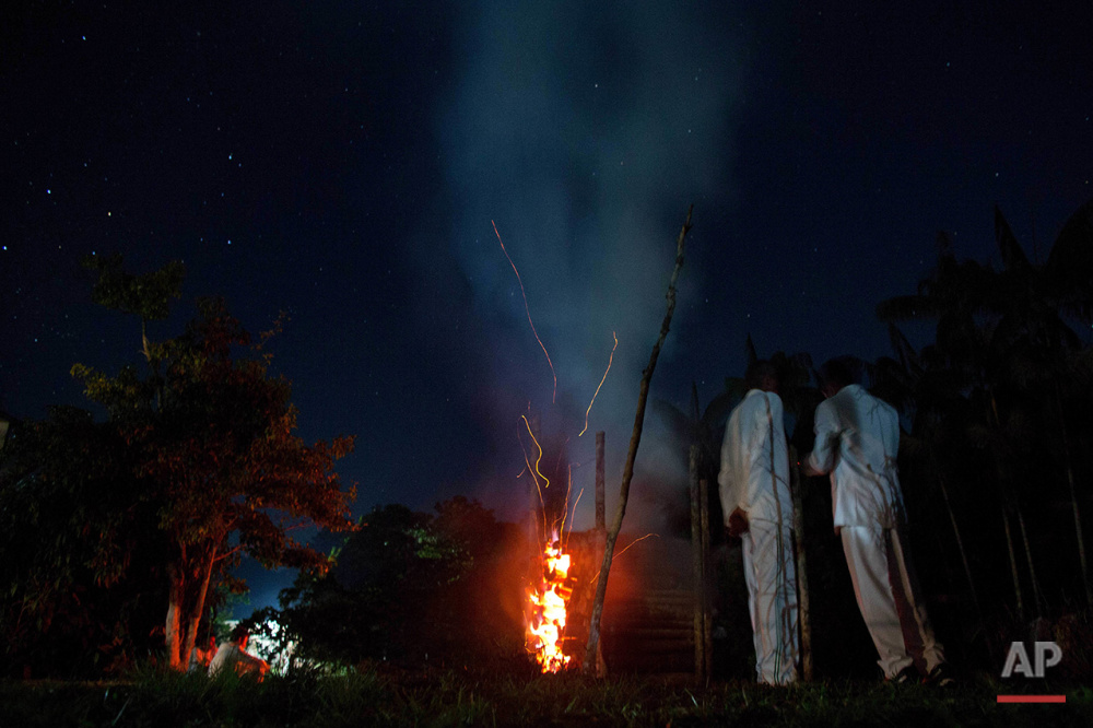 In this June 22, 2016 photo, church members of the doctrine of the Holy Daime warm themselves next to a bonfire during a break in the service in Ceu do Mapia, Amazonas state, Brazil. The community revolves around an ancient psychedelic tea locals know as the Holy Daime. The Ayahuasca brew is sacred to the villagers, who use it in rituals that blend together Indian beliefs with Roman Catholicism. (AP Photo/Eraldo Peres)