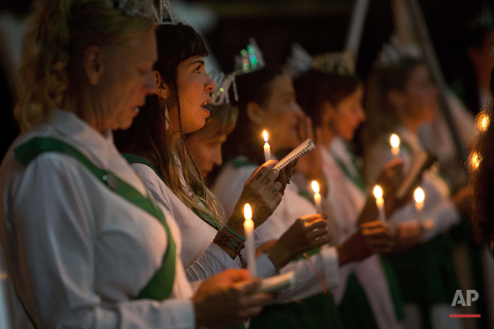 In this June 22, 2016 photo, women hold candles during a religious service in the church of the doctrine of Holy Daime, in Ceu do Mapia, Amazonas state, Brazil. At the church men and women line up in two separate rows to drink the tea after making the sign of the cross. They then sing together prayers and psalms in a large circle. (AP Photo/Eraldo Peres)