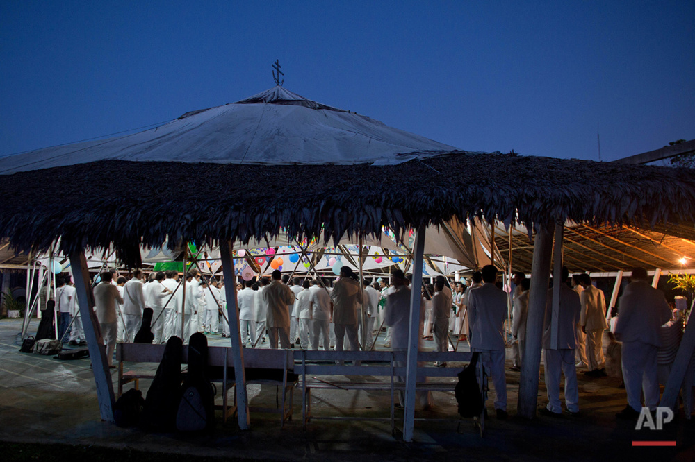 In this June 23, 2016 photo, members of church of the doctrine of Holy Daime stand during a religious service, at dawn, in Ceu do Mapia, Amazonas state, Brazil. Most services last all night and into the morning. (AP Photo/Eraldo Peres)