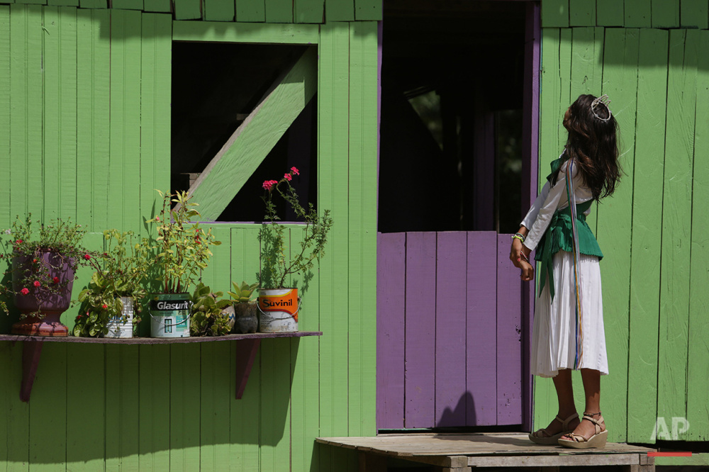 In this June 22, 2016. photo, 12-year-old Maria Clara, preens in front of her house before going to the religious service of Holy Daime in Ceu do Mapia, Amazonas state, Brazil. The whole village gathers to celebrate the Brazilian harvest and the feast of Saint John. Women wear shiny white crowns on their heads, green sashes over their shoulders and green belts around their waist. (AP Photo/Eraldo Peres)