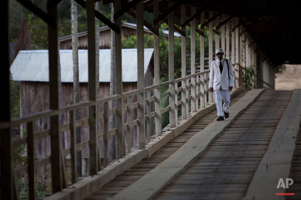 In this June 22, 2016 photo, a man dressed in white walks on the community's main bridge to participate in the Holy Daime ritual in Ceu do Mapia, Amazonas state, Brazil. Men and women gather in the local church to celebrate the Brazilian harvest and the feast of Saint John. (AP Photo/Eraldo Peres)