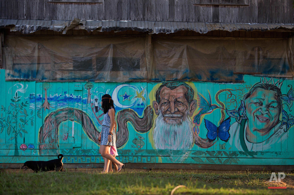 In this June 23, 2016 photo, girls walk in front of a mural with images of the founder of the Ceu do Mapia community, Godfather Sebastiao, and his wife Godmother Rita, at Ceu do Mapia, Amazonas state, Brazil. In the early 1980s rubber tapper Sebastiao Mota de Melo, nicknamed Godfather Sebastiao, took hundreds of followers deep into the forest to create a new village that would live by the Ayahuasca tea doctrine. Melo passed away in 1990, but his wife, who is now 91, still heads the sect with her two sons. (AP Photo/Eraldo Peres)