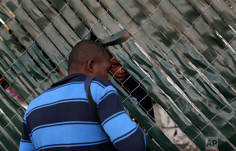In this Oct. 3, 2016 photo, a Haitian woman talks to a fellow migrant, from behind the fence of the Padre Chava migrant shelter in Tijuana, Mexico. The man was not able to enter the overcrowded shelter. (AP Photo/Gregory Bull)