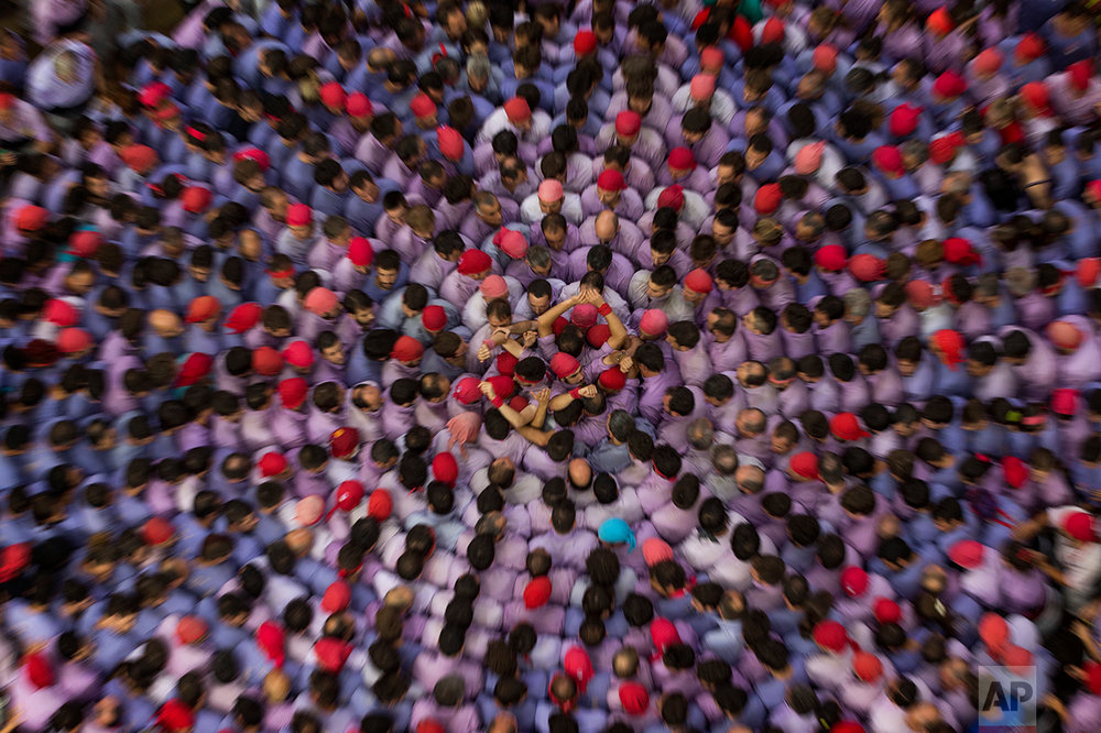 """In this Sunday, Oct. 2, 2016 photo, members of the Marrecs de Salt form the base to make their human tower during the 26th Human Tower Competition in Tarragona, Spain. The tradition of building human towers, or Castells, dates back to the 18th century and takes place during festivals in Catalonia. """"Colles,"""" or teams, compete to build the tallest and most complicated towers. The structure of the castells varies depending on their complexity. (AP Photo/Emilio Morenatti)"""