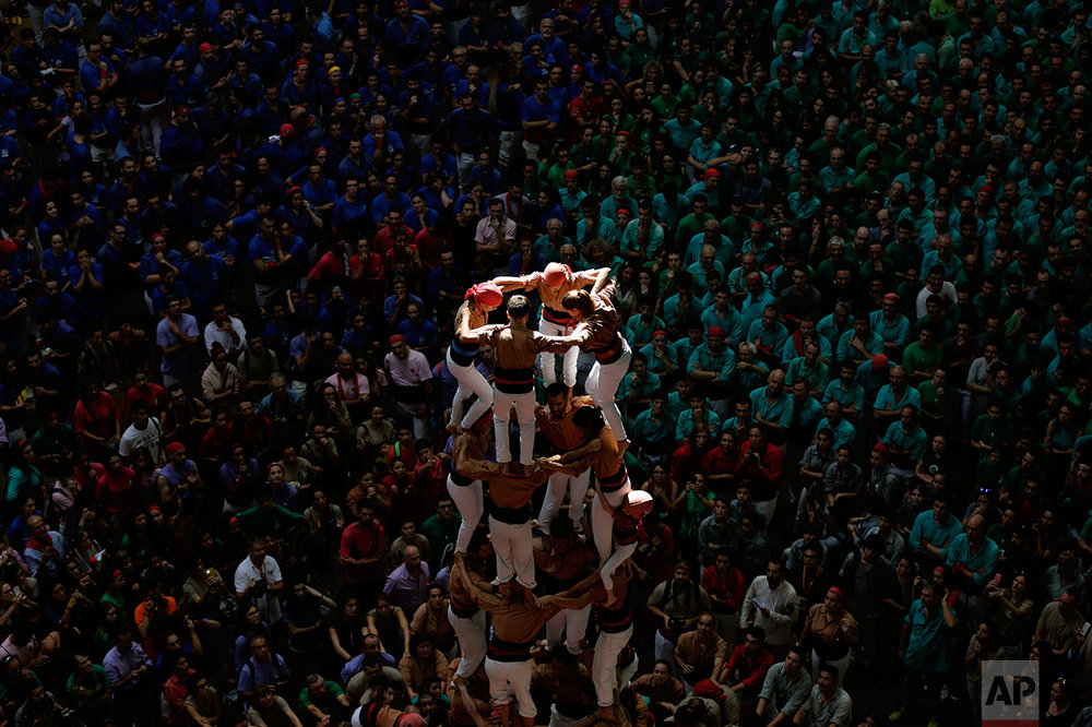 """In this Sunday, Oct. 2, 2016 photo, members of the colla Xiquets de Reus form their human tower during the 26th Human Tower Competition in Tarragona, Spain. The tradition of building human towers, or Castells, dates back to the 18th century and takes place during festivals in Catalonia. """"Colles,"""" or teams, compete to build the tallest and most complicated towers. The structure of the castells varies depending on their complexity. (AP Photo/Emilio Morenatti)"""