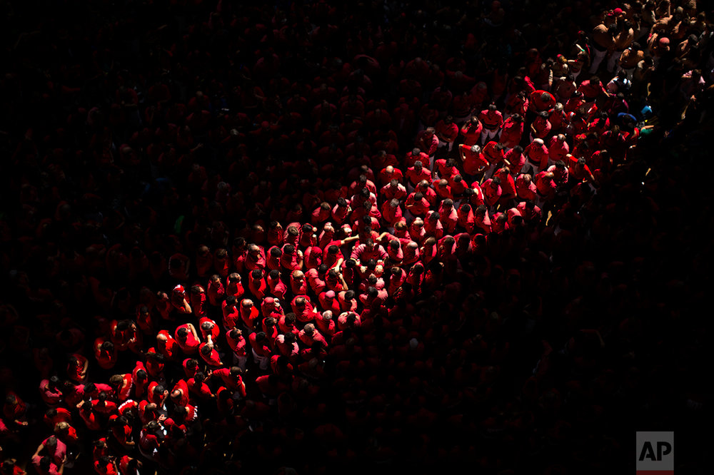 """In this Sunday, Oct. 2, 2016 photo, members of the """"colla Vella de Valls"""" form a base to construct a human tower during the 26th Human Tower Competition in Tarragona, Spain. The tradition of building human towers, or Castells, dates back to the 18th century and takes place during festivals in Catalonia. """"Colles,"""" or teams, compete to build the tallest and most complicated towers. The structure of the castells varies depending on their complexity. (AP Photo/Emilio Morenatti)"""