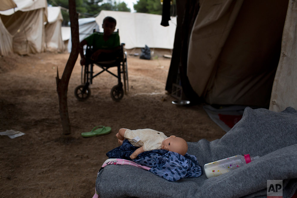 In this Monday, Sept. 19, 2016 photo, 15-year-old Ahmed Khalil Isa, a disabled Syrian teenager, sits in his wheelchair outside his family's tent at the Ritsona camp for refugees and other migrants north of Athens. The family from Al Hasakah in Syria reached the Greek island of Chios on an overcrowded dinghy from Turkey on March 13, 2016, and have since been stranded in Greece.They were planning to reach Germany, where  many of their relatives already live. (AP Photo/Petros Giannakouris)
