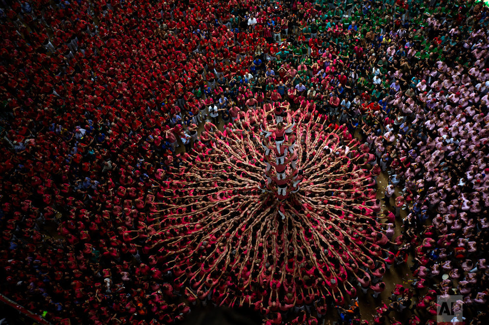 "Members of ""Vella de Xiquets de Valls"" try to complete their human tower during the 26th Human Tower Competition in Tarragona, Spain, on Sunday, Oct. 2, 2016. The tradition of building human towers, or Castells, dates back to the 18th century and takes place during festivals in Catalonia, where ""colles,"" or teams, compete to build the tallest and most complicated towers. The structure of the castells varies depending on their complexity. A castell is considered completely successful when it is loaded and unloaded without falling apart. The highest castell in history was a 10 floor structure with 3 people in each floor. In 2010 castells were declared by UNESCO one of the Masterpieces of the Oral and Intangible Heritage of Humanity. (AP Photo/Emilio Morenatti)"