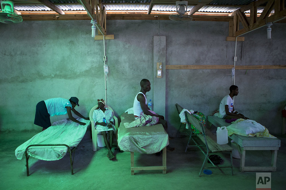 The daughter of 84-year-old Armant Germain replaces the sheets on her bed, in the cholera ward at a hospital in Les Cayes Haiti, Tuesday, Oct. 11, 2016. Health authorities have warned that Hurricane Matthew has created conditions that are likely to cause an increase in the deadly waterborne cholera disease. (AP Photo/Rebecca Blackwell)