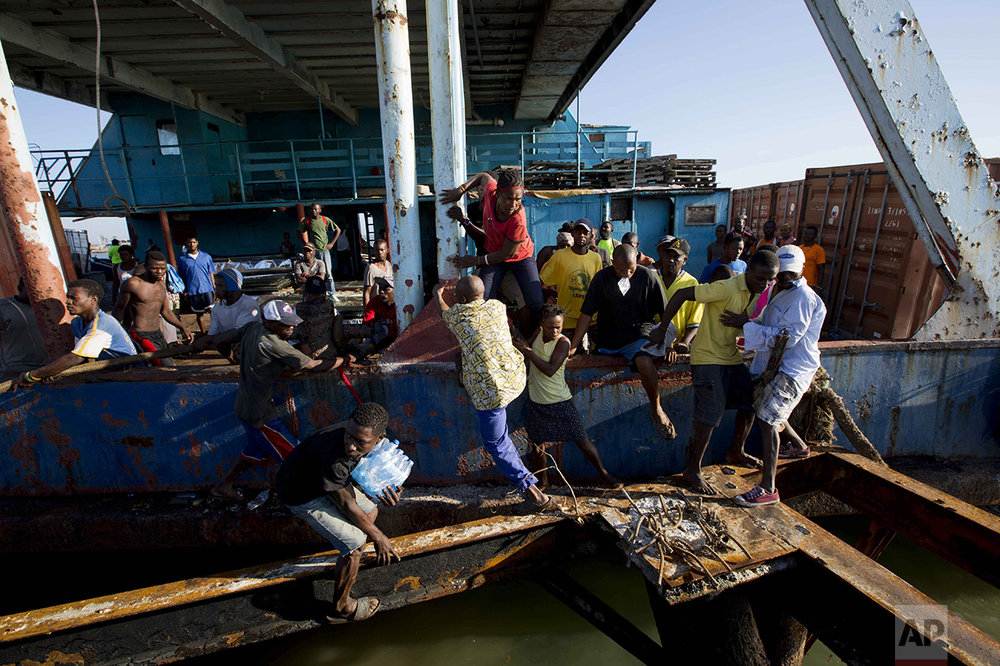 "People try to get off a boat carrying aid as national police arrive to secure the vessel carrying supplies as it docks in Jeremie, Haiti, Wednesday Oct. 12, 2016, after Hurricane Matthew hit the area. The U.N. envoy for Haiti says the impoverished Caribbean nation is facing ""a humanitarian tragedy and an acute emergency situation"" with 1.4 million people needing immediate help. (AP Photo/Dieu Nalio Chery)"