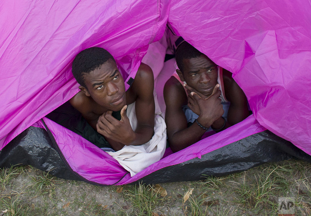 Young men whose home was destroyed by Hurricane Matthew peer out of a tent as they awake for the day in the courtyard of a school where they have sought shelter, in Port Salut, Haiti, Monday, Oct. 10, 2016. While some families were able to recover mattresses, furniture, and a few household goods from under the mud, others lost everything. The scores of people sheltering at this school have been told they have one more week before they have to move out so classes can restart. (AP Photo/Rebecca Blackwell)