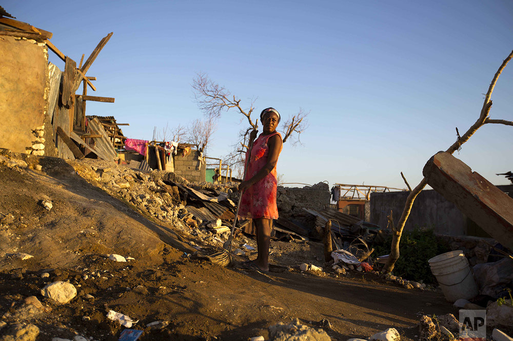 A woman pauses as she sweeps the ground where her home once stood after the passing of Hurricane Matthew in Jeremie, Haiti, Wednesday, Oct. 12, 2016. Nearly a week after the storm smashed into southwestern Haiti, some communities along the southern coast have yet to receive any assistance, leaving residents who have lost their homes and virtually all of their belongings struggling to find shelter and potable water. (AP Photo/Dieu Nalio Chery)
