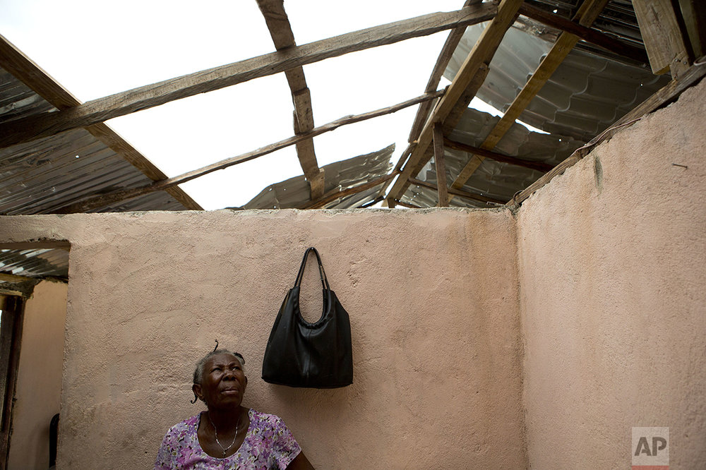 A woman looks up as a worker uses salvaged sheets of mangled metal, full of holes, to create a makeshift roof atop her home damaged by Hurricane Matthew, in Port-a-Piment, Haiti, Monday, Oct. 10, 2016. (AP Photo/Rebecca Blackwell)
