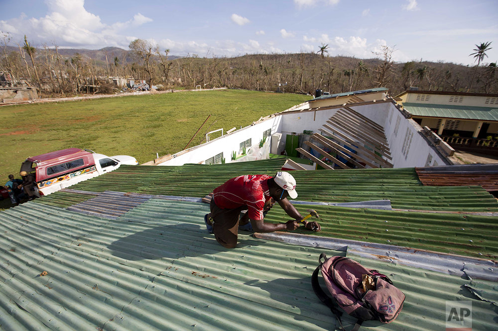A man repairs a roof that was destroyed by Hurricane Matthew in Dame-Marie, Haiti on Monday, Oct. 10, 2016. (AP Photo/Dieu Nalio Chery)