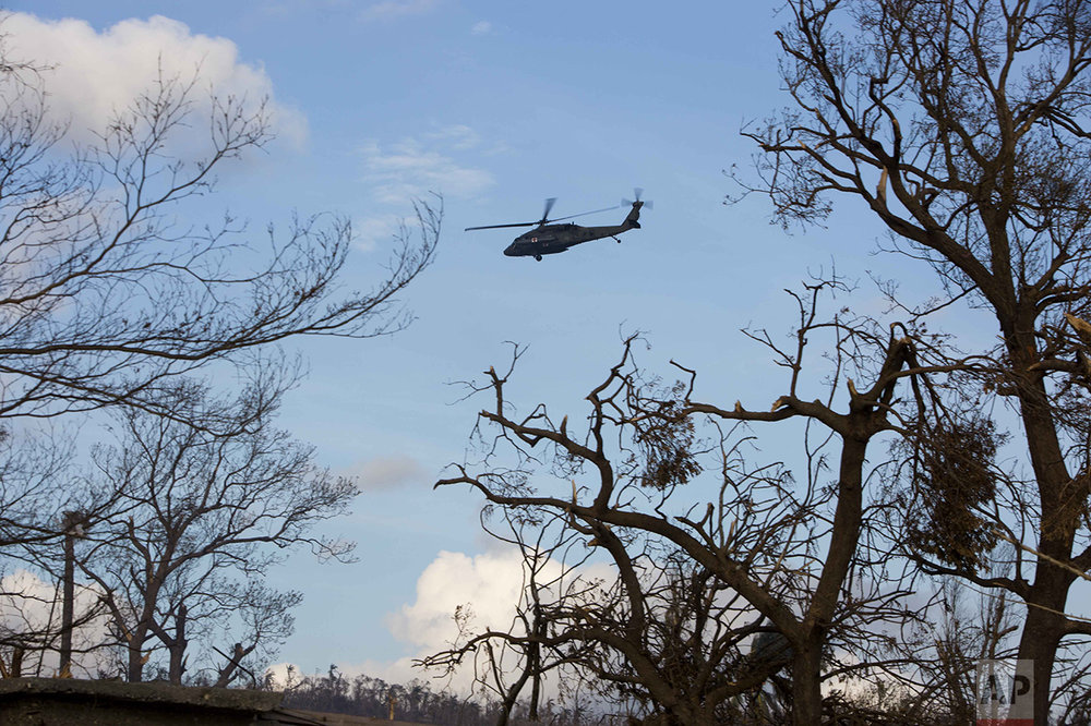 A United States armed forces helicopter flies past in Dame-Marie, Haiti on Monday, Oct. 10, 2016. (AP Photo/Dieu Nalio Chery)