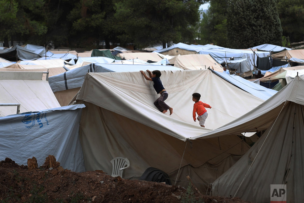 Children play at the top of a tent at Ritsona refugee camp north of Athens, which hosts about 600 refugees and migrants on Thursday, Sept. 8, 2016. The refugee crisis is expected to be a central issue in discussions Friday at a meeting in Athens of leaders from Mediterranean countries in the European Union. (AP Photo/Petros Giannakouris)