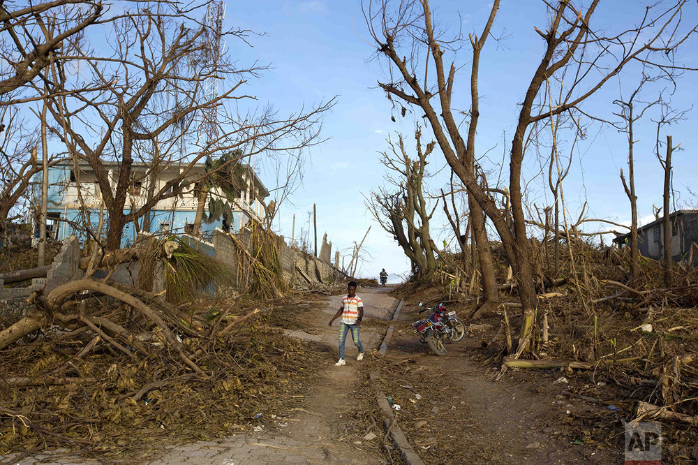 A man walks past debris left by Hurricane Matthew in Dame-Marie, Haiti, Monday, Oct. 10, 2016. Nearly a week after the storm smashed into southwestern Haiti, some communities along the southern coast have yet to receive any assistance, leaving residents who have lost their homes and virtually all of their belongings struggling to find shelter and potable water. (AP Photo/Dieu Nalio Chery)
