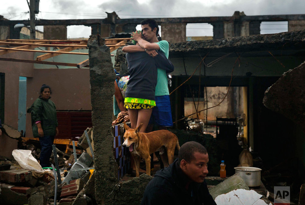 A couple embrace standing among the debris of their home destroyed by Hurricane Matthew in Baracoa, Cuba, Wednesday, Oct. 5, 2016. The hurricane rolled across the sparsely populated tip of Cuba overnight, destroying dozens of homes in Cuba's easternmost city, Baracoa, leaving hundreds of others damaged.  (AP Photo/Ramon Espinosa)