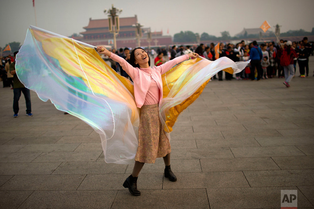 A woman dances with flags at Tiananmen Square on National Day in Beijing, Saturday, Oct. 1, 2016. Saturday marks the 67th anniversary of the founding of the People's Republic of China. (AP Photo/Mark Schiefelbein)