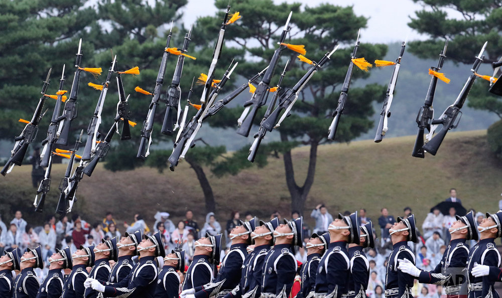 Members of a South Korean military honor guard throw their guns into the air during the 68th anniversary of Armed Forces Day at the Gyeryong military headquarters in Gyeryong, South Korea, Saturday, Oct. 1, 2016. (AP Photo/Lee Jin-man)
