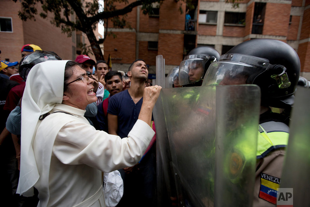 In this Friday, Sept. 16, 2016 photo, a nun confronts Bolivarian National Police officers as they block demonstrators during an opposition protest in Caracas, Venezuela. The opposition called for protests across the country to demand from the government clear legal conditions for the collection of voter signatures that would enable a recall referendum on the mandate of Venezuela's President Nicolas Maduro. (AP Photo/Fernando Llano)