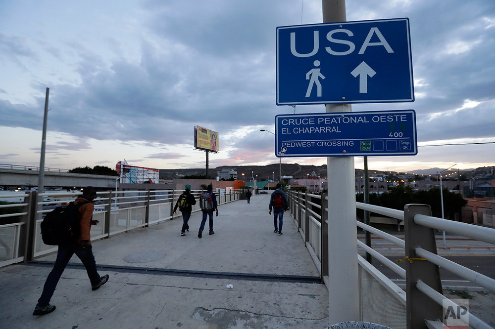 In this Sept. 27, 2016 photo, Haitians make their way towards the border crossing in Tijuana, Mexico. U.S. officials say about 5,000 Haitians showed up at San Ysidro from October 2015 through late last month, and Immigration and Customs Enforcement Director Sarah Saldana said at a recent congressional hearing that officials told her on a trip to Central America that 40,000 more were on their way. (AP Photo/Gregory Bull)