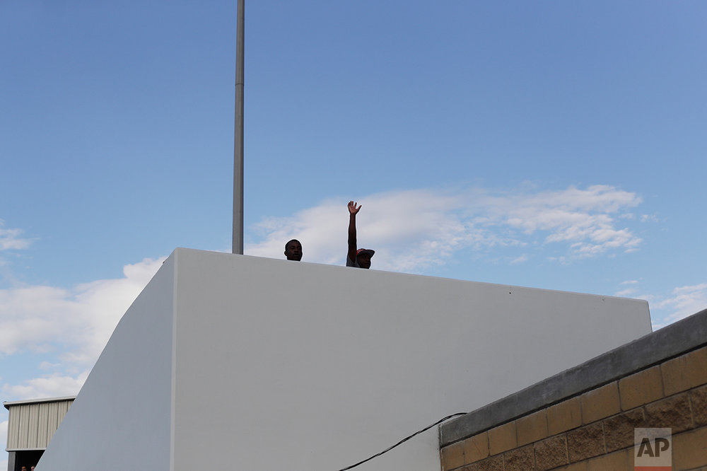 In this Sept. 27, 2016 photo, a Haitian migrant waves on his way to the U.S. border crossing, in Tijuana, Mexico. The U.S. Department of Homeland Security on Sept. 22 halted the humanitarian parole it had given Haitians following a massive 2010 earthquake. Instead of releasing the Haitians into the United States, under a general policy the U.S. is now confining them to a detention facility and it plans to start deporting them back to the homeland they hoped to flee. (AP Photo/Gregory Bull)