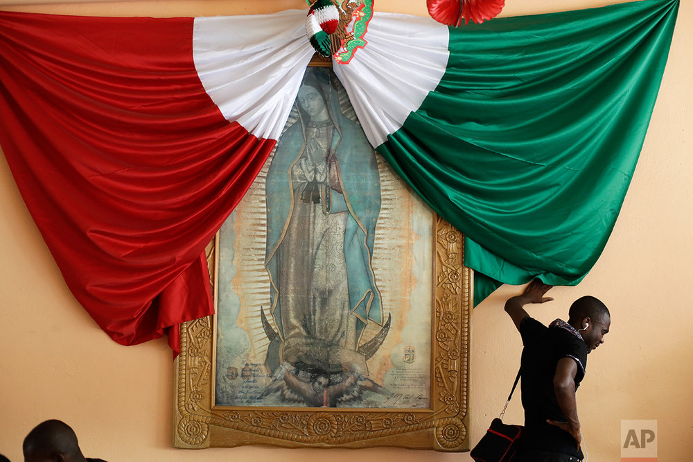 In this Sept. 26, 2016 photo, a Haitian man listening to music on his phone and leaning against a wall decorated with a Mexican national flag and a framed image of the Virgin of Guadalupe, waits for a bed at the Padre Chava migrant shelter in Tijuana, Mexico. Many Haitians arriving at the U.S. border with Mexico are unaware of a new U.S. policy of putting them in deportation proceedings and detaining them while making efforts to fly them home. (AP Photo/Gregory Bull)