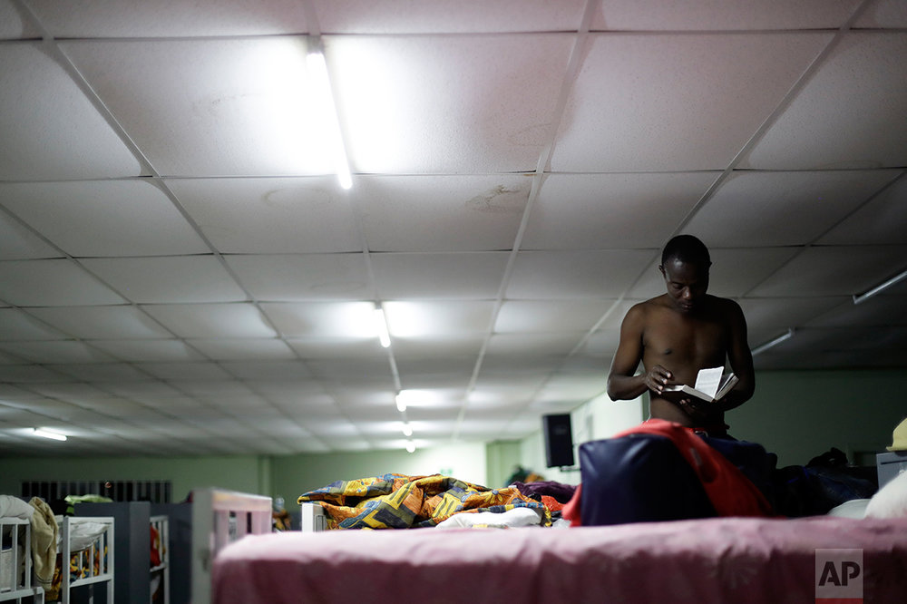 In this Sept. 26, 2016 photo, a Haitian migrant reads a Bible at the Padre Chava migrant shelter, in Tijuana, Mexico. Padre Chava, one of 10 Tijuana shelters that house Haitians, turned away hundreds over the weekend, leading many to sleep outside on cardboard sheets. (AP Photo/Gregory Bull)