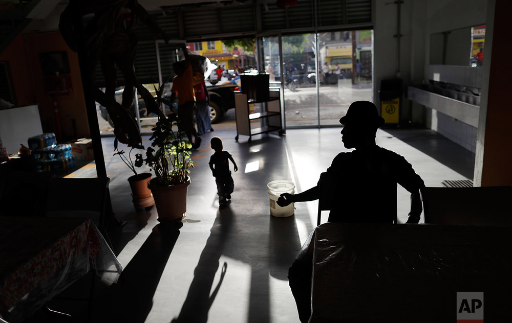 In this Sept. 26, 2016 photo, a Haitian man returns a ball to a boy at the Padre Chava migrant shelter, in Tijuana, Mexico. Padre Chava, one of 10 Tijuana shelters that house Haitians, turned away hundreds over the weekend, leading many to sleep outside on cardboard sheets. (AP Photo/Gregory Bull)