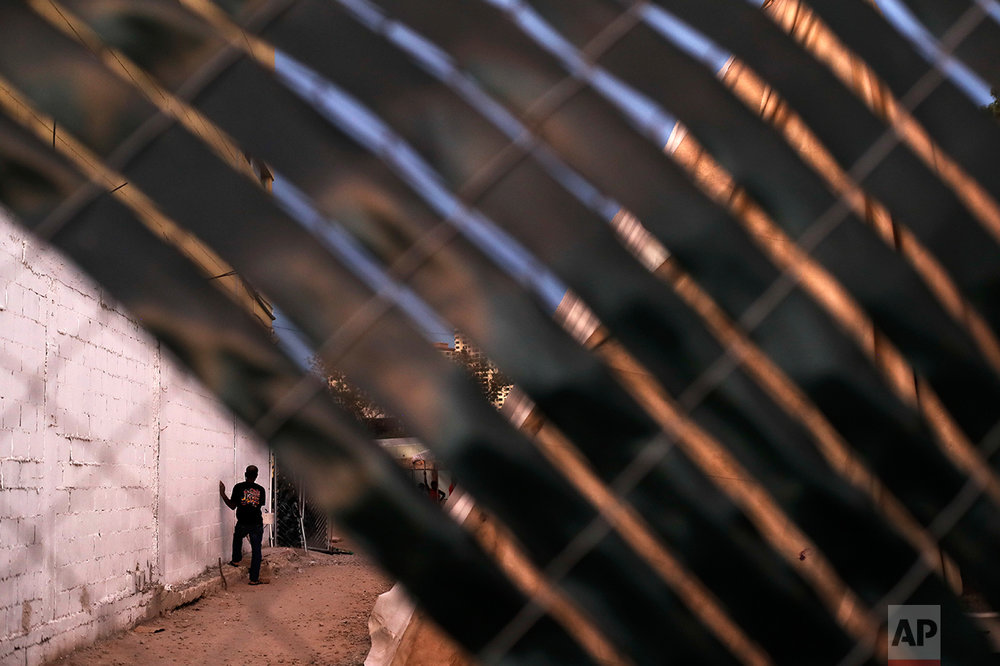 In this Sept. 26, 2016 photo, a Haitian migrant waits along a wall at the Padre Chava migrant shelter as diner is served inside, in Tijuana, Mexico.  U.S. officials say about 5,000 Haitians showed up at San Ysidro from October 2015 through late last month. (AP Photo/Gregory Bull)