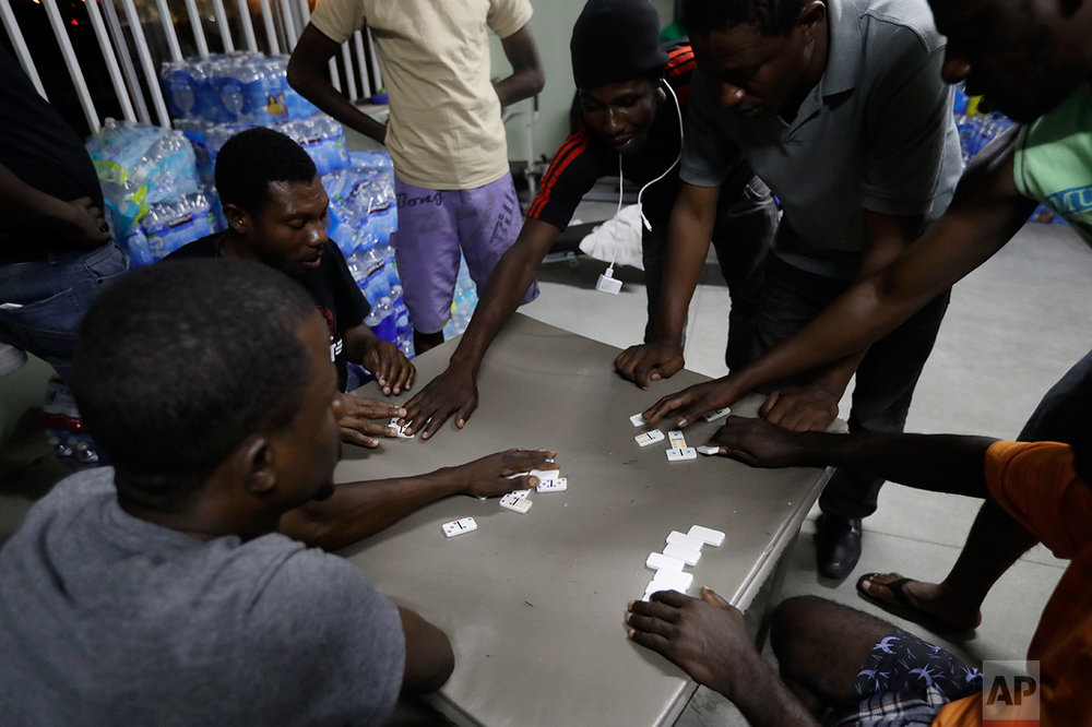 "In this Sept. 26, 2016 photo, Haitian migrants play dominoes at the Padre Chava migrant shelter, in Tijuana, Mexico. ""We are exhausted, completely exhausted,"" said shelter administrator Margarita Andonaegui. ""When we have more than 200 people, we lose control."" (AP Photo/Gregory Bull)"