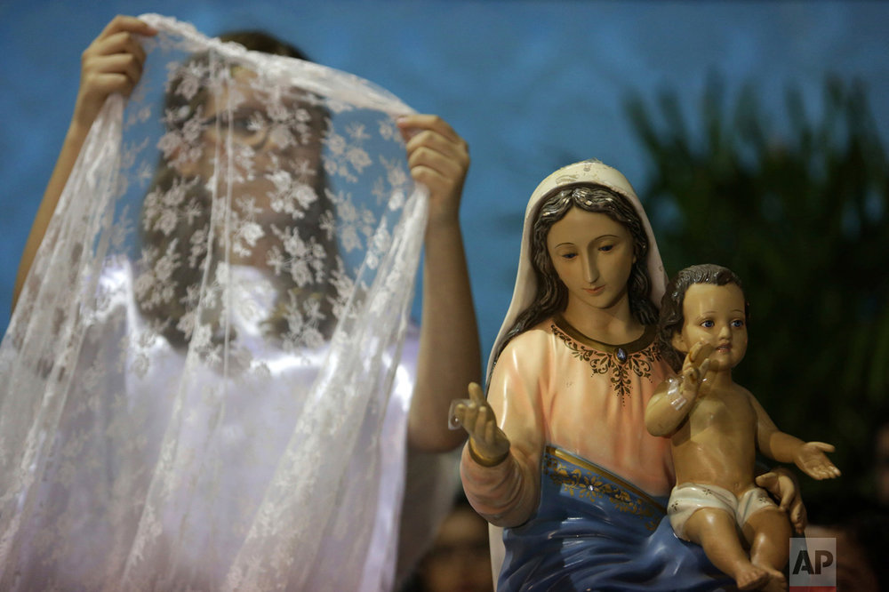 In this Oct. 7, 2016 photo, a girl prepares to place a veil on a statue of Our Lady of the Rosary during the annual Afro-Christian Congada celebration in Catalao, Goias state, Brazil. According to local legend, the ritual was first performed by Black slaves in the 1800s in Brazil where the Catholic icon, Our Lady of the Rosary, is associated with the African divinity Yemanja, or Sea Mother. (AP Photo/Eraldo Peres)