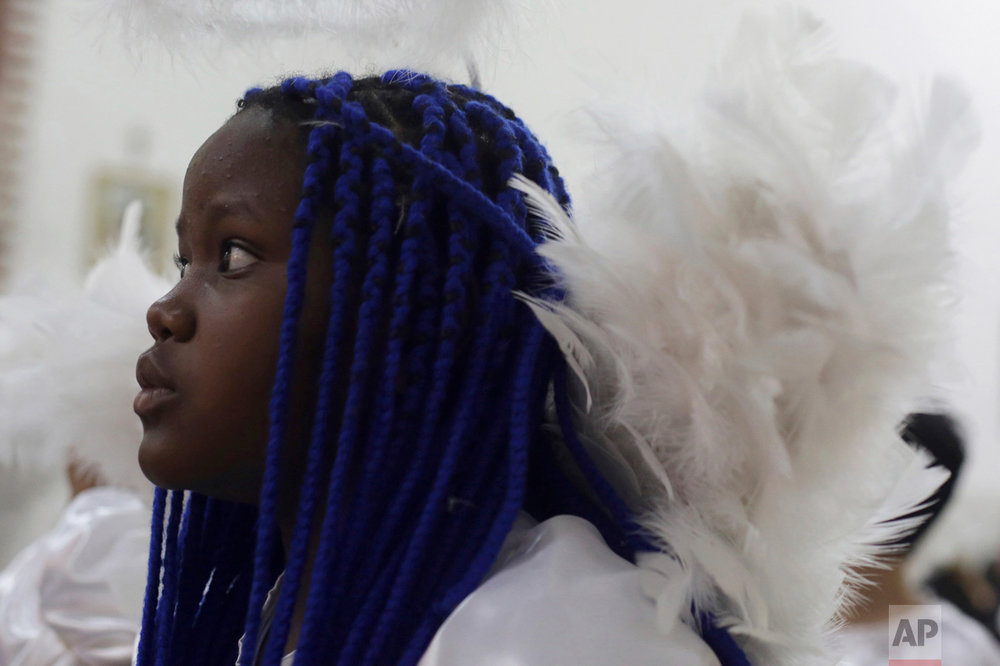 In this Oct. 7, 2016 photo, a girl dressed as an angel attends a Mass in honor of Our Lady of Rosario during the annual Afro-Christian Congada celebration in Catalao, Goias state, Brazil. Some children participate in the annual celebration dressed as angels, considered a sacred symbol representing purity. (AP Photo/Eraldo Peres)