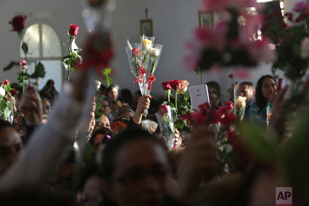 In this Oct. 8, 2016 photo, people hold up flowers during a Mass in honor of Our Lady of the Rosary during the annual Afro-Christian Congada celebration in Catalao, Goias state, Brazil. After Mass people place their flowers at the statue of the virgin, who represents the African divinity Yemanja, or Sea Mother. (AP Photo/Eraldo Peres)