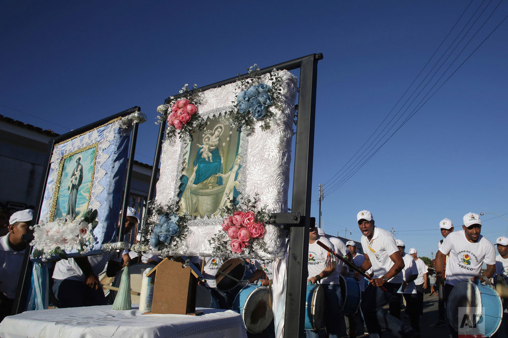 In this Oct. 8, 2016 photo, drummers perform behind images of Saint Benedict, left, and Our Lady of the Rosary, during the annual Afro-Christian Congada celebration in Catalao, Goias state, Brazil. The Congada, an annual tradition on the second Sunday of October, combines elements from the Catholic Church and African traditions, a testament to the mixing of cultures, religions and races in Latin America's largest nation. (AP Photo/Eraldo Peres)
