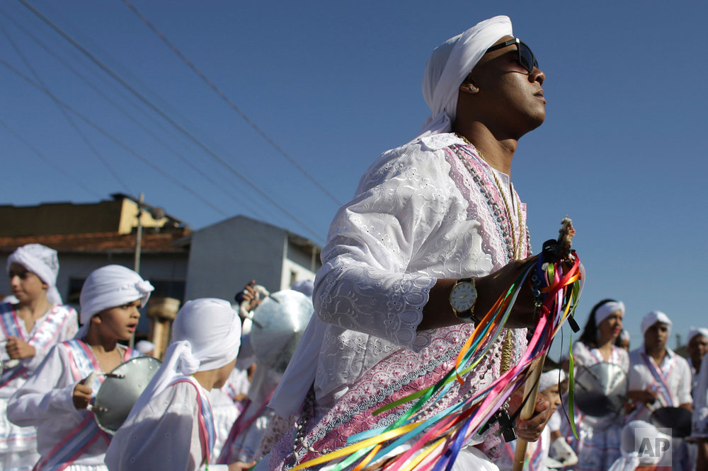 In this Oct. 9, 2016 photo, Matheus Alves, captain of the Mozambique Our Lady of the Rosary dance group, performs during the annual Afro-Christian Congada celebration in Catalao, Goias state, Brazil. His turban is the signature of Mozambique dance group, as they pay tribute to St. Benedict and Our Lady of the Rosary. These Catholic icons are associated with African deities Yemanja, or Sea Mother, and Ossaim, a god of nature. (AP Photo/Eraldo Peres)