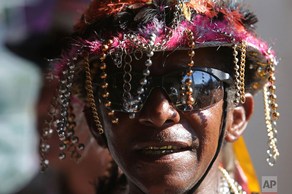 In this Oct. 9, 2016 photo, a man in costume performs during the annual Afro-Christian Congada celebration in Catalao, Goias state, Brazil.  The dance and drumming ritual was initially performed by groups of black slaves brought to Brazil during colonial times to work on plantations under Portuguese rule. (AP Photo/Eraldo Peres)