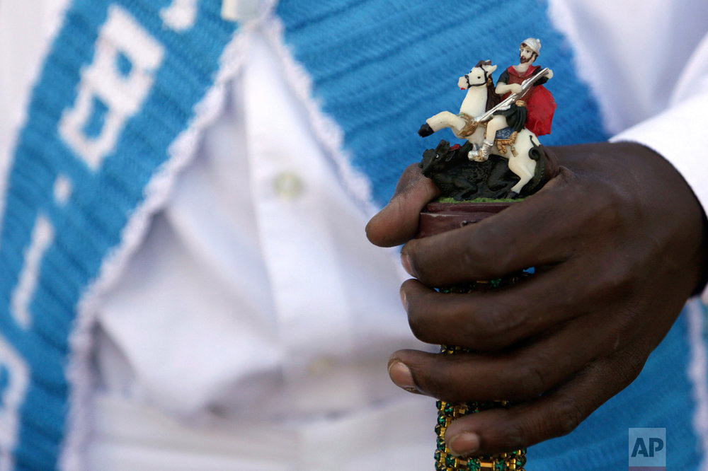 In this Oct. 9, 2016 photo, a man holds a walking cane decorated with a statue of St. George during an annual Afro-Christian dance tradition called Congada, in Catalao, Goias state, Brazil. St. George is one of the most important and popular saints in Brazilian, and is associated with Ogun, an African deity of war. (AP Photo/Eraldo Peres)