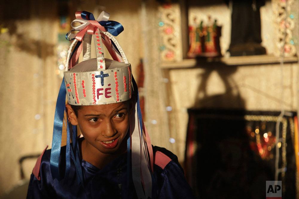"In this Oct. 9, 2016 photo, a young dancer with a hat that reads ""Faith"" in Portuguese performs with others by an altar outside a home during the annual Afro-Christian Congada celebration in Catalao, Goias state, Brazil. Families offer food to performers who dance from Our Lady of the Rosary church as a way to fulfill a promise. (AP Photo/Eraldo Peres)"