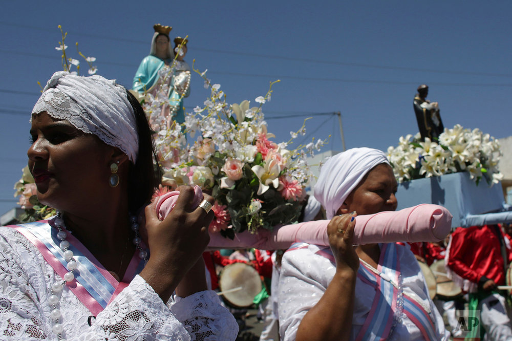 In this Oct. 9, 2016 photo, women carry statues of Our Lady of the Rosary and St. Benedict during the annual Afro-Christian Congada celebration in Catalao, Goias state, Brazil. Our Lady of the Rosary represents the African divinity Yemanja, or Sea Mother, and St. Benedict corresponds to the African divinity Ossaim, a god of nature. (AP Photo/Eraldo Peres)